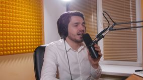 Radio and live broadcast concept. Young man with headphones talking on mic, online radio. Radio and live broadcast concept. Young man with headphones talking on stock footage