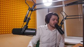 Radio and live broadcast concept. Young man with headphones talking on mic, online radio. Radio and live broadcast concept. Young man with headphones talking on stock video footage