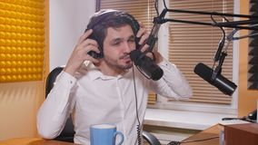 Radio and live broadcast concept. Young man with headphones talking on mic, online radio. Radio and live broadcast concept. Young man with headphones talking on stock video