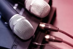 Radio microphones. wireless sound transmission system. Microphones are on the receiver. Audio wires are connected. Soft focus Two mic stock image