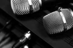 Radio microphones. wireless sound transmission system. Microphones are on the receiver. Audio wires are connected. soft focus Two mic. black and white stock images