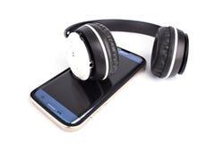 Radio moderna y smartphone de los auriculares aislados en la parte posterior del blanco foto de archivo