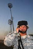 Radio operator with antennas. A US soldier, wearing a helmet, talking on a radio with three antennas behind him at dawn or dusk