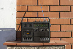 Radio outside. A vintage transistor radio sitting outside on a wall stock image
