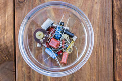 Radio parts in the glassy saucer on the wooden table. The radio parts in the glassy saucer on the wooden table. View from above stock photography