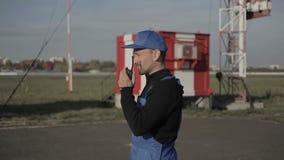 Radio portátil del uso del trabajador del aeropuerto y mano de las ondas metrajes