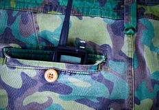 Radio portatile in una tasca dei pantaloni con il modello del cammuffamento tonnellata Fotografie Stock