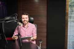 Radio presenter hosting a show. Portrait of smiling hispanic male radio presenter with clipboard hosting a show at radio station Stock Images
