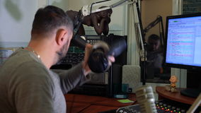 Radio presenter at the microphone in a live radio broadcast studio stock video footage