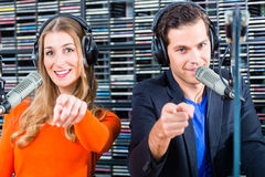 Radio presenters in radio station on air. Presenters or moderators - men and women - in radio station hosting show for radio live in Studio Royalty Free Stock Image