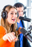 Radio presenters in radio station on air. Presenters or moderators - men and women - in radio station hosting show for radio live in Studio Stock Photos