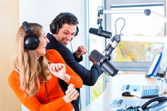 Radio presenters in radio station on air. Presenters or moderators - men and women - in radio station hosting show for radio live in Studio Stock Images