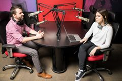 Radio presenters in studio hosting a live show live. Young men and women presenters in radio station hosting a live radio show Royalty Free Stock Photos
