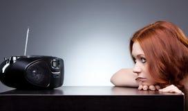 Radio que escucha de la mujer joven imagenes de archivo