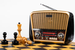 Radio receiver in retro style with chess pieces on chessboard and white background Stock Image