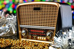 Radio receiver in retro style with christmas decorations on bokeh lights background Royalty Free Stock Photo