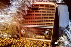 Radio receiver in retro style with christmas decorations and light beams on black background Stock Photography