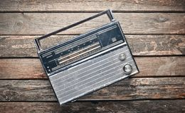Radio receiver from the 70s on a rustic wooden background. Top view Stock Photos