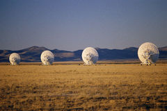 Radio telescope dishes scattered in field Stock Image