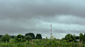 Radio tower on a background cloudy summer sky hyperlapse. Cloudy sky and field. Landscape radio tower in a field on a background cloudy sky. Movement clouds stock video