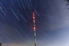 Radio tower with star trails. This radio tower is complemented by star trails resulting from consecutive pictures of 80 minutes Royalty Free Stock Photos