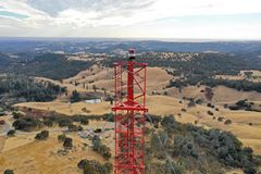 Radio tower top. Parallel vertical view of the top section of a red steel radio tower against a distant landscape and sky view background royalty free stock images