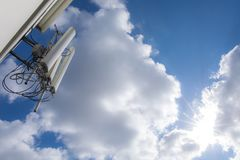 Radio, tv or telephone transmitter with blue sky clouds and sunlight. stock photos