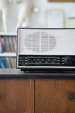 Radio on wooden table and bookshelf background. Vintage radio on wooden table and bookshelf background Stock Photos