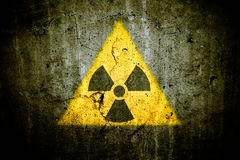 Radioactive atomic nuclear ionizing radiation danger warning symbol in triangular shape painted massive cracked concrete wall. Radioactive atomic nuclear stock images