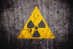 Radioactive atomic nuclear ionizing radiation danger warning symbol on concrete wall dark background royalty free stock images