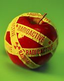 Radioactive Food Apple. Radioactive apple on a green background stock photo