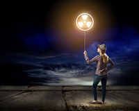 Radioactive hazard. Young woman in casual holding balloon with radioactivity sign royalty free stock image