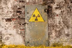 Radioactive ionizing radiation danger symbol painted on the old massive rusted iron door. Of an abandoned structure with grunge walls and overall derelict Royalty Free Stock Photo