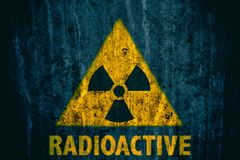 Radioactive ionizing radiation danger symbol with word radioactive below painted on a massive concrete wall. Triangular yellow and black radioactive ionizing Royalty Free Stock Photos