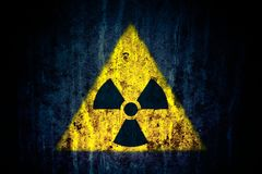 Radioactive ionizing radiation nuclear danger yellow symbol on massive cracked concrete wall dark rustic grunge background Royalty Free Stock Photography