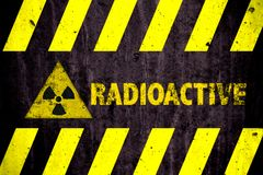 Radioactive ionizing radiation or nuclear energy danger symbol word yellow hazard black stripes painted on concrete. Radioactive ionizing radiation or nuclear royalty free stock image
