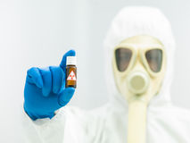 Radioactive isotope sample. In a small brown bottle with a warning label held in the fingers of a laboratory scientist in full protective clothing with a mask Stock Image