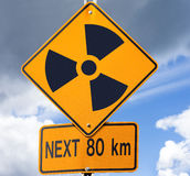 Radioactive road sign. Road sign with radioactivity warning symbol on it with dramatic sky background Royalty Free Stock Image
