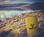 Radioactive Waste Near Water. Conceptual Image Of A Radioactive Nuclear Waste Barrel Or Drum Near Water In The Countryside Royalty Free Stock Image