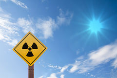 Radioactivity warning symbol on blue sky backgroun Stock Images