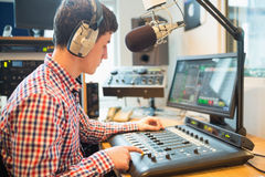 Radiogastheer die correcte mixer in studio met behulp van Royalty-vrije Stock Foto's