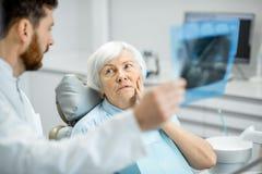 Radiografía de la demostración del dentista a la más vieja mujer en la oficina del dentall fotografía de archivo libre de regalías