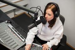 Radiojockey Using Music Mixer terwijl het Communiceren op Microfoon stock fotografie