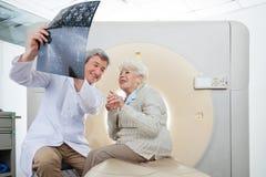 Radiolog With Patient Looking på CT-bildläsningen Arkivfoto