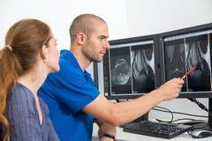Radiolog som councelling en patient som använder bilder från tomograpy eller MRI Royaltyfri Bild