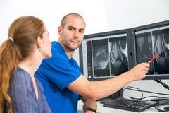 Radiolog som councelling en patient som använder bilder från tomograpy eller MRI Royaltyfria Bilder