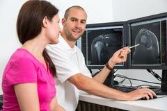 Radiolog som councelling en patient som använder bilder från tomograpy eller MRI Royaltyfri Fotografi