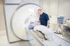 Radiologa kładzenia zwitka Na Patient& x27; s głowa Przechodzi MRI obraz cyfrowego Zdjęcia Royalty Free