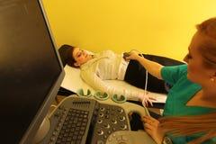 Radiologic техник и женский пациент лежа на CT просматривают кровать стоковое фото