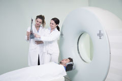 Radiologic technician and Patient being scanned and diagnosed on scanner Royalty Free Stock Images